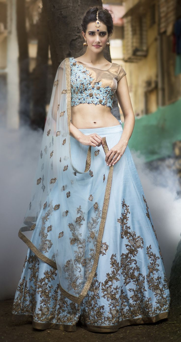 Featuring this hand crafted blue raw silk lehenga encrusted with beading, crystals,sequin and bugle beads with mesmerising motives. The attire finishes with ant