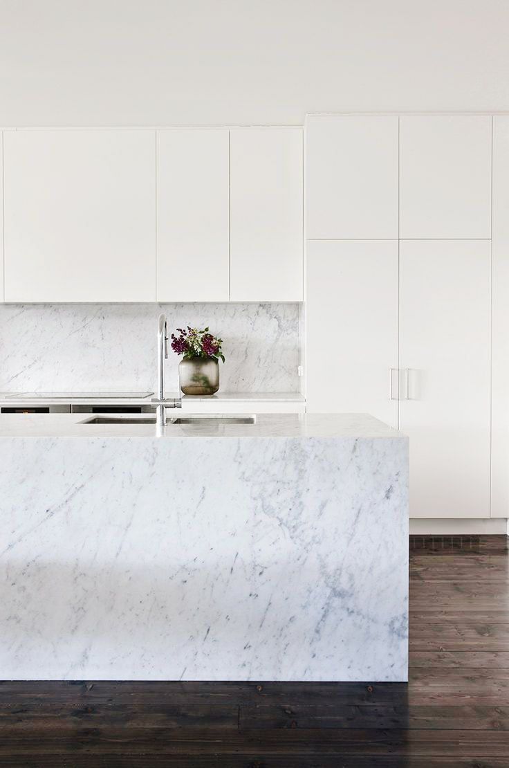 White, marble kitchen with sleek features and small floral arrangement