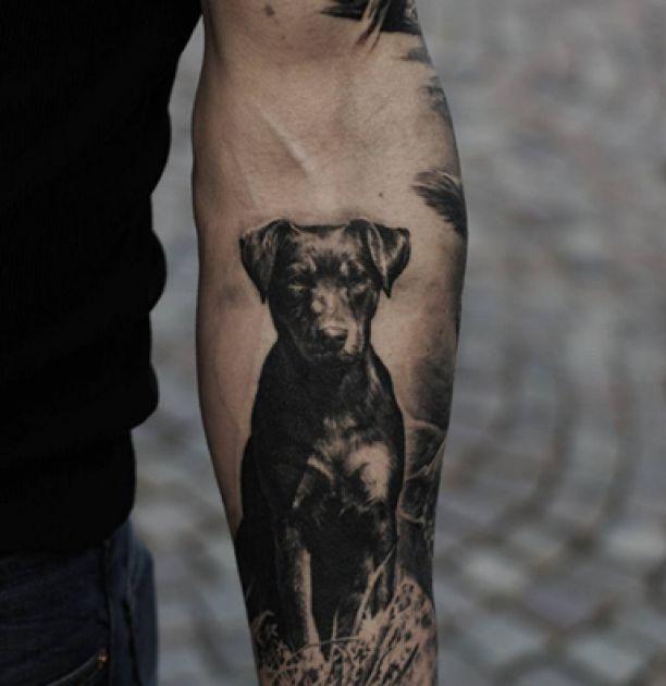 Tattoo schwarzer Hund auf Unterarm