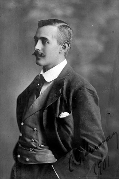 A man pictured (1901) in a three-piece suit including a contrasting double-breasted waistcoat with a pocket watch