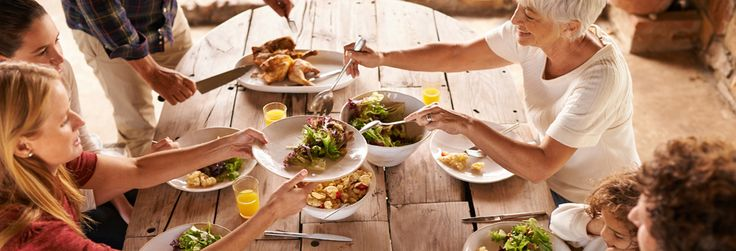 Family sharing a meal of salad and chicken at a rustic wooden table