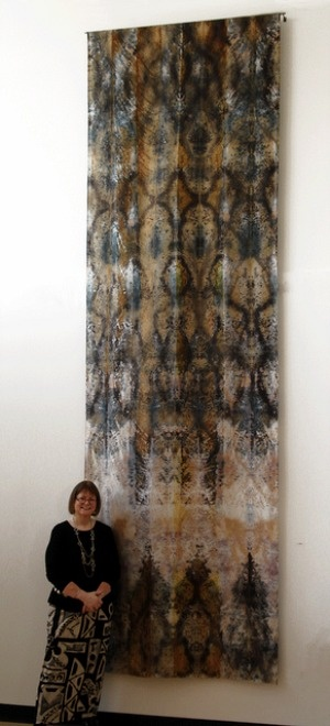 Textile artist Pat Vivod stands before her wall hanging 'Pond Ripples' (2010). Shibori rusted Silk Dupioni with elderberries & turmeric, 14.5 feet x 55 in. via Illinois SDA