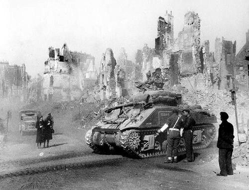 A pall of dust rises from the ruins of Caen, Normandy, France as a Canadian Sherman tank passes through on its way to join the attack towards Falaise.