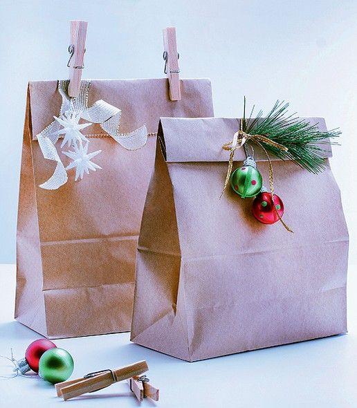 Pacotes de papel kraft decorados com elementos festivos deixam a base da árvore estilosa