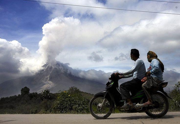 Indonesian villagers ride on a motorbike as mount Sinabung spews volcanic smoke as seen from Jeraya village in Karo, North Sumatra, Indonesi...