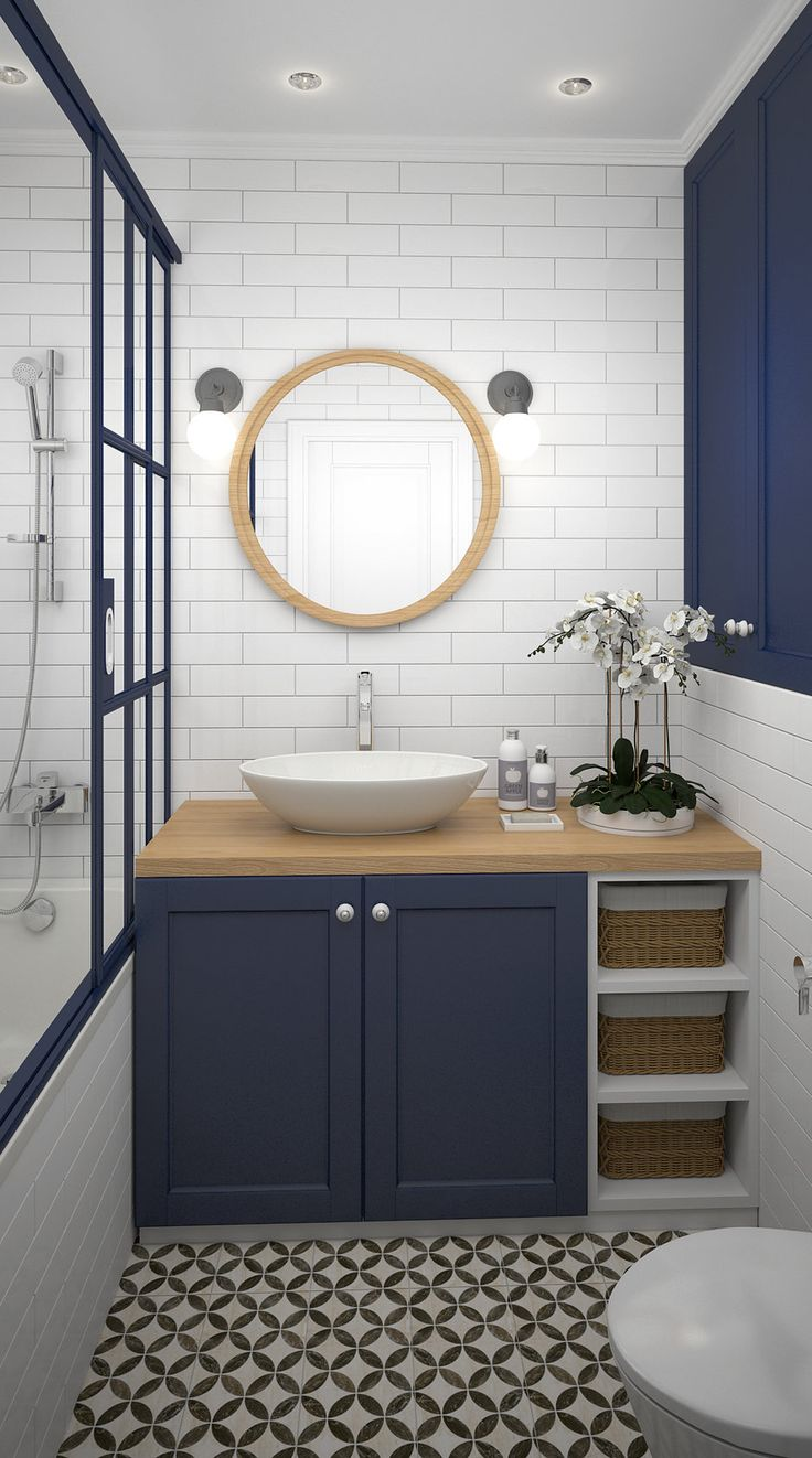 Contrast of the circular mirror, sink, and floor pattern to the rectangular subway tiles on the wall. Contrast of the dark blue cabinets to the white tiled walls