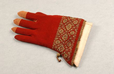 "The coloured fingertips are way too cute!  ""An embroidered glove of red knitted silk, probably liturgical, probably English, first half 17th century with wide low gauntlet of gold embroidered and couched thread flowerheads with looped and couched petals, chain stitched lozenges, large single tassel to one side, 24 cm long"""