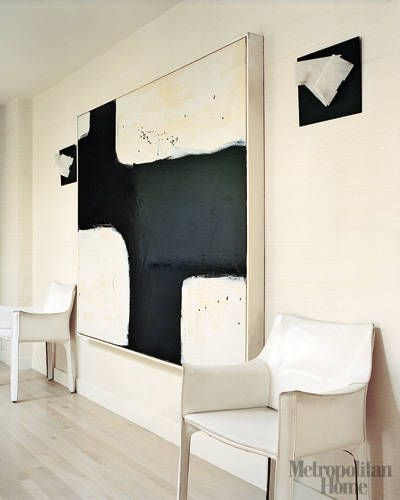 White Leather Chairs by Mario Bellini A pair of Cassina's Cab chairs by Mario Bellini in white leather and the bold graphics of a black-and-white abstract painting complement the warm white walls and bleached walnut floors.