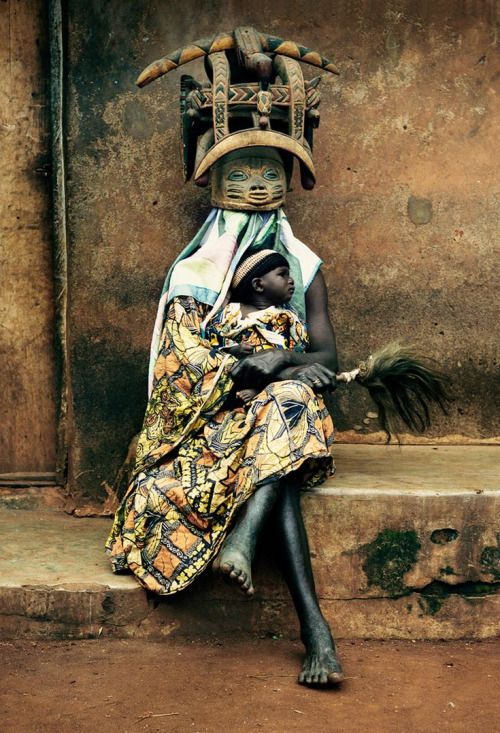 """Baba Ichanga"" wearing traditional gelede mask and holding a baby, evoking the…"