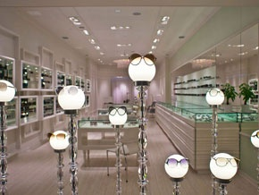 whimsical eyewear display - illuminated glass lamp globes stand in as mannequins.