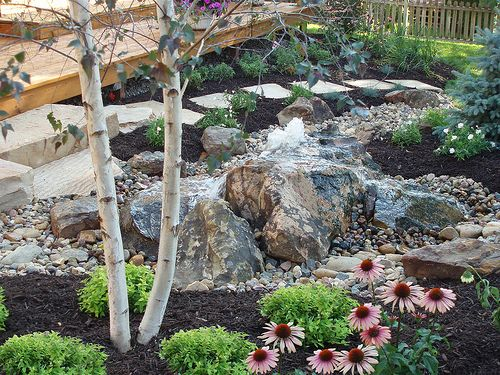 Omaha backyard landscape featuring bubbling rock, river bed, boulders