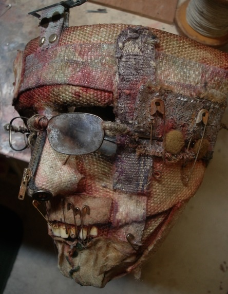 textures of the mask, burlap, layers, pins, bits and pieces of easily found household items