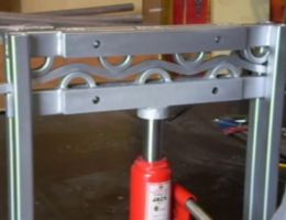 Homemade stair baluster bender comprised of half-round dies mounted on a hydraulic press.