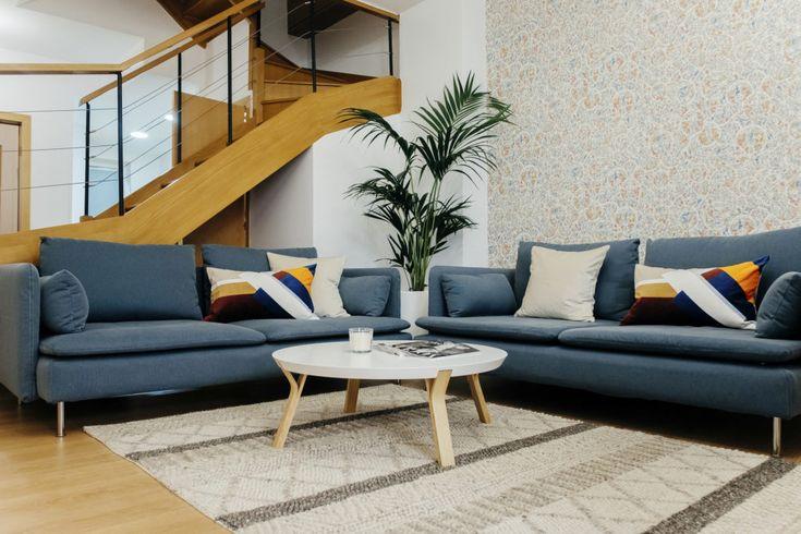 Sofá en azúl, mesa en blanco con patas en haya y la alfombra de lana, hacen un conjunto de salón con estilo nórdico.