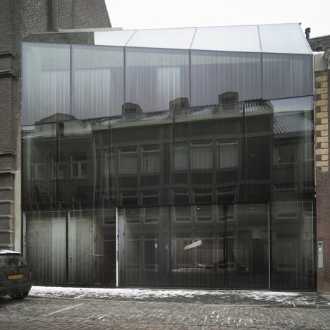 A collection of vintage Aston Martins can be glimpsed through the fritted glass facade of this house