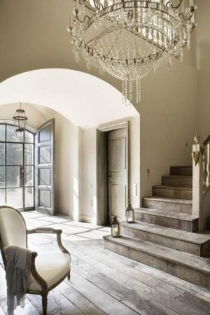 Entrada con techo abovedado y suelo y escalera de madera rústica.