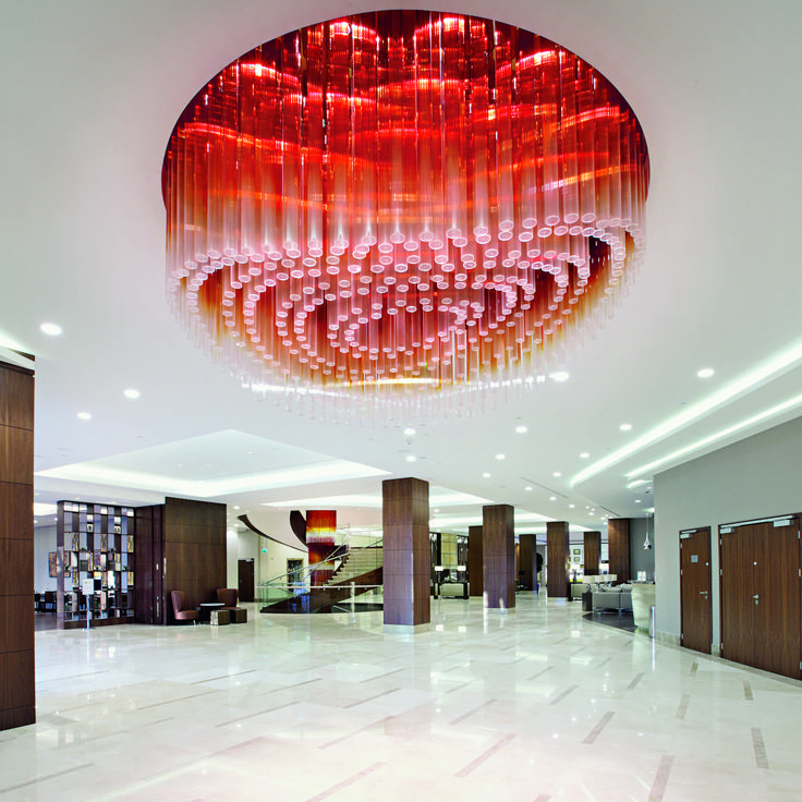 The Hilton Hotel and Convention Center in Warsaw greets guests with striking installations on every corner. The hotel's main entrance is illuminated by a 7-m wide chandelier fabricated from optical glass tubes ranging in colour from clear crystal to amber. #light #lighting #design #interior #crystal #chandelier #pendant #hospitality #hotel