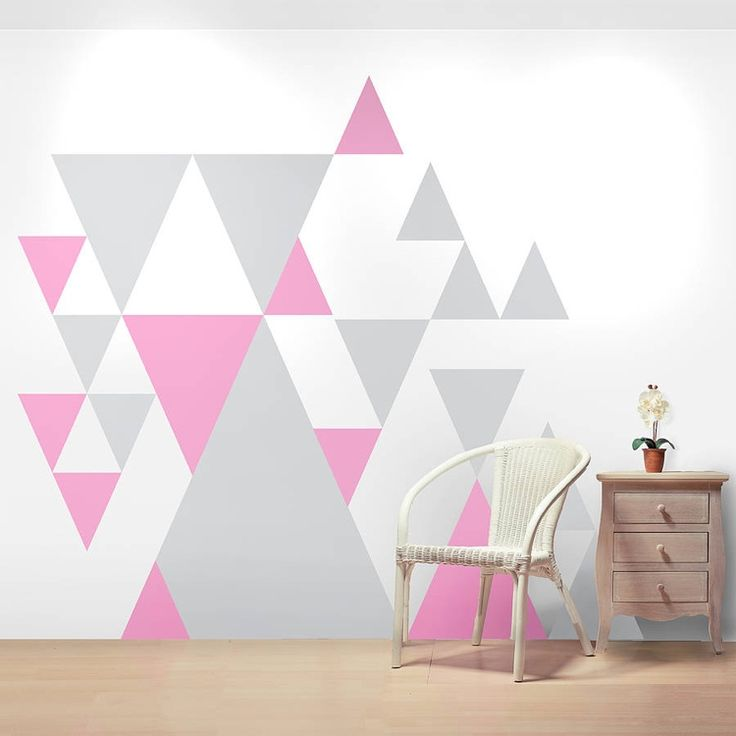 des triangles en rose et gris en tant que décoration murale géométrique dans la chambre à coucher