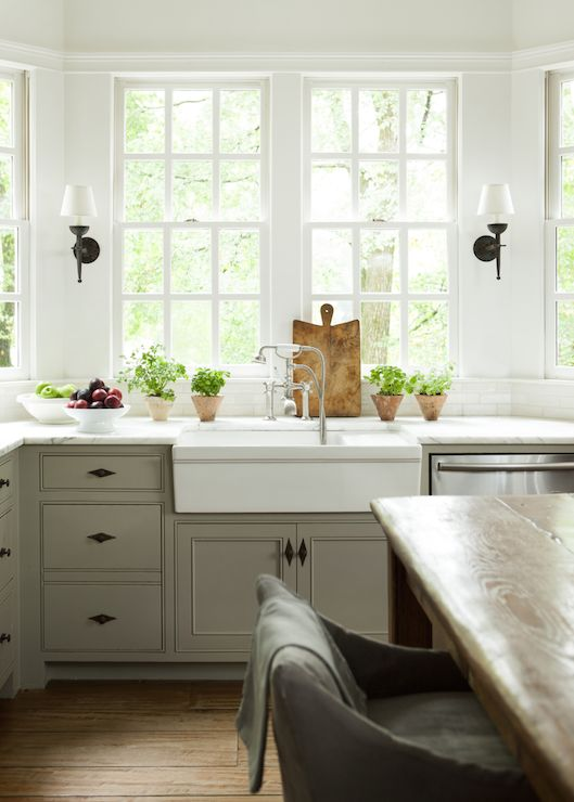 Lovely kitchen features a farmhouse island lined with grays slipcovered counter stools situated across from white apron sink and vintage pull out faucet beside stainless steel dishwasher under bay window lit by oil rubbed bronze sconces.