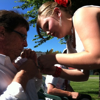 Jordyn putting a boutonnière on her and the grooms father.