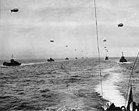 "NORMANDY INVASION - A convoy of Landing Craft Infantry sails across the English Channel toward the Normandy Invasion beaches on ""D-Day"", 6 June 1944. Each of these landing craft is towing a barrage balloon for protection against low-flying German aircraft. Among the LCI(L)s present are: LCI(L)-56, at far left; LCI(L)-325; and LCI(L)-4."