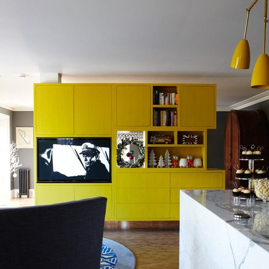 Use a room divider A bold, eclectic approach works well in an open room as there is space to breathe. A bespoke yellow cabinet acts as a room divider between living and dining areas, while still maintaining an open feel. This is also a good way to introduce a hit of colour to a plain colour scheme. This cleverly designed unit also stores the television, books and glassware. Yellow cabinet Chamber Furniture