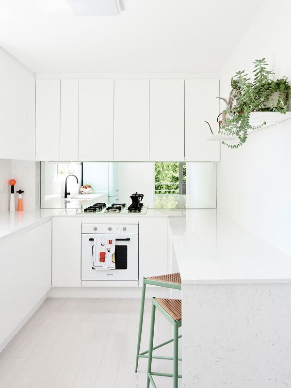 White eat-in kitchen: white handleless cabinets, mirror splashback, white stone benchtop, white oven, pale limewashed floorboards, sage green bar stools, breakfast bar, indoor plants on wall-mounted shelf