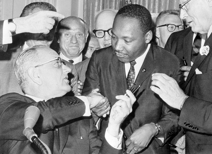 President Lyndon Johnson shakes hands with Reverend Martin Luther King, Jr., on July 3, 1964 in Washington, District of Columbia, after handing him a pen during the ceremonies for the signing of the civil rights bill at the White House.