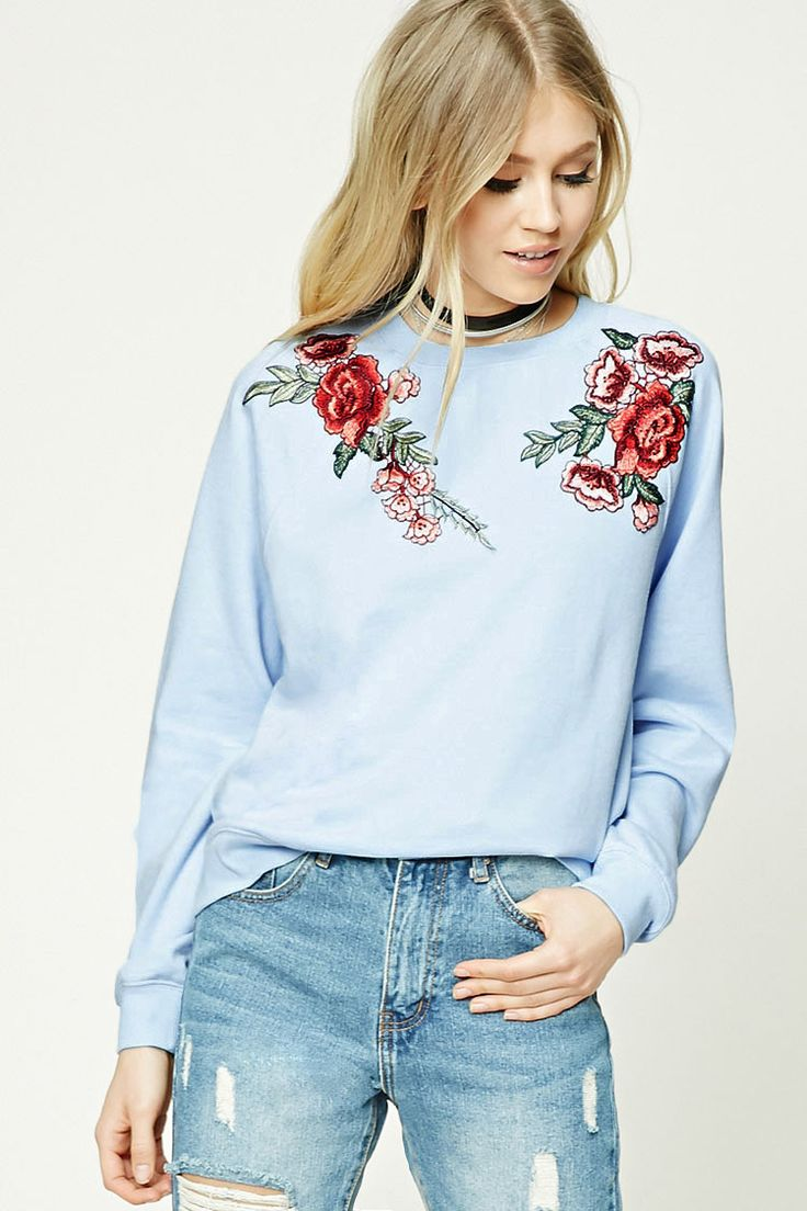 A French terry knit sweatshirt featuring a rose embroidery, round neckline, long raglan sleeves, and a ribbed trim.
