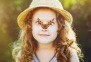 Surprised girl with a butterfly on her nose, focus on a girl's face. Background toning to instagram filter.