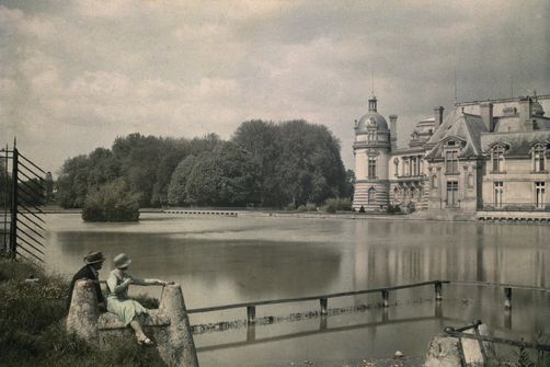 Chantilly, Oise. A couple relaxes by the pond with a view of Chateau de Chantilly. Photographer: JULES GERVAIS COURTELLEMONT