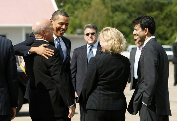 President Barack Obama puts his arm around Lt. Gov. Mitch Landrieu as Louisiana Senator Mary Landrieu (D-LA) (C) and Governor Bobby Jindal (R) watch upon Obama's arrival to New Orleans October 15, 2009