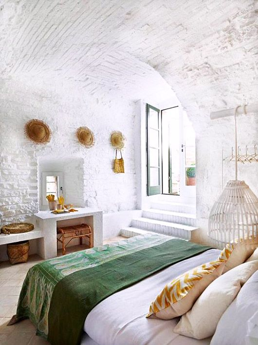 All white brick bedroom with pops of green