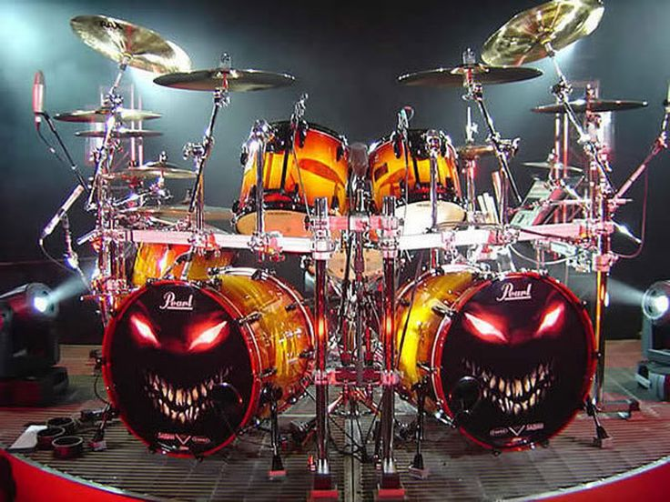 Pearl drums with eerie Halloween jack o'lantern style glowing grin, red eyes, lots of white teeth drum set for band Disturbed with their art on heads.