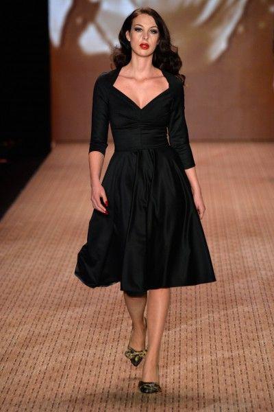 Lena Hoschek FW 2014/15 Berlin Fashion Week: Model trägt schwarzes Kleid mit V Ausschnitt und weitem Rock