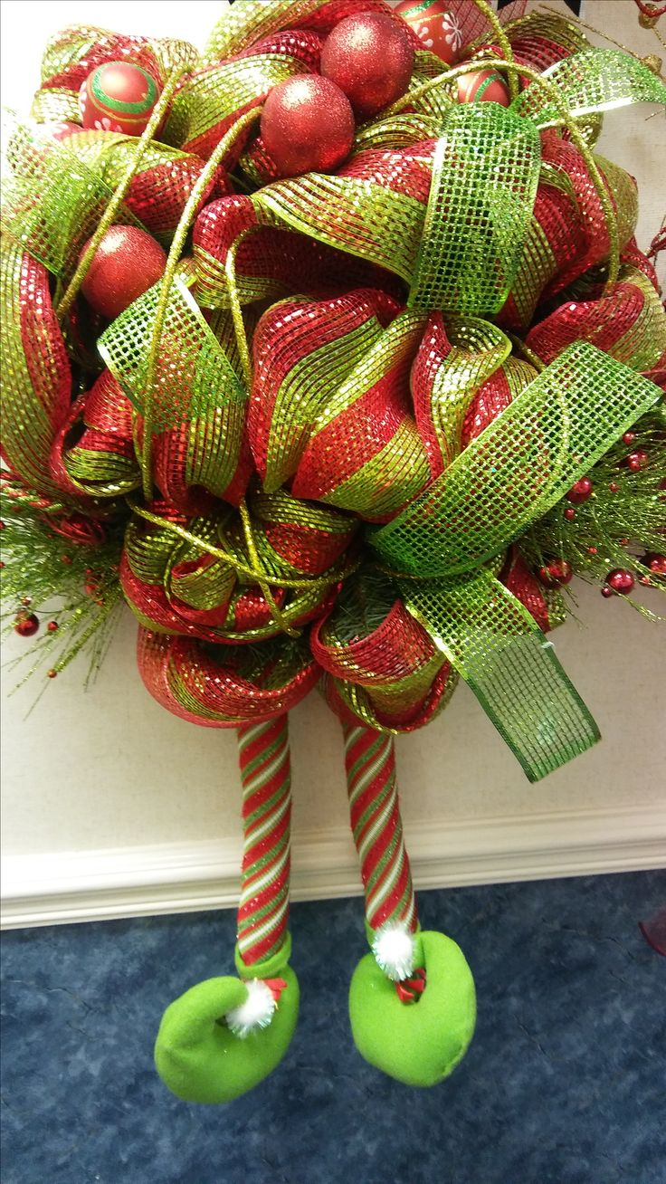 """Christmas Elf Wreath with Legs. Great way to brighten up your doorway for the Holiday Season. Designed with reds & greens to make it even more festive. The elf legs hang about 17"""" from the base of the which is approximently 21"""" in length."""