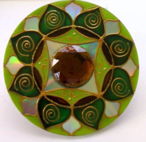 Mandala feita em CD reciclado. Tamanho de 12cm de diâmetro. Pintura vitral, decorado com pedra acrílica e tinta relevo dourada. Com gancho de metal para ser pendurada na parede.  As cores são muito utilizadas no Feng Shui. Elas irradiam determinadas curas, pois cada cor vibra em determinada freqüência, mesmo que não possamos perceber. Este é um dos motivos porque em determinados lugares nos sentimos bem e em outros não.   Verde: saúde. Equilibra as emoções, ativa o poder de cura e…
