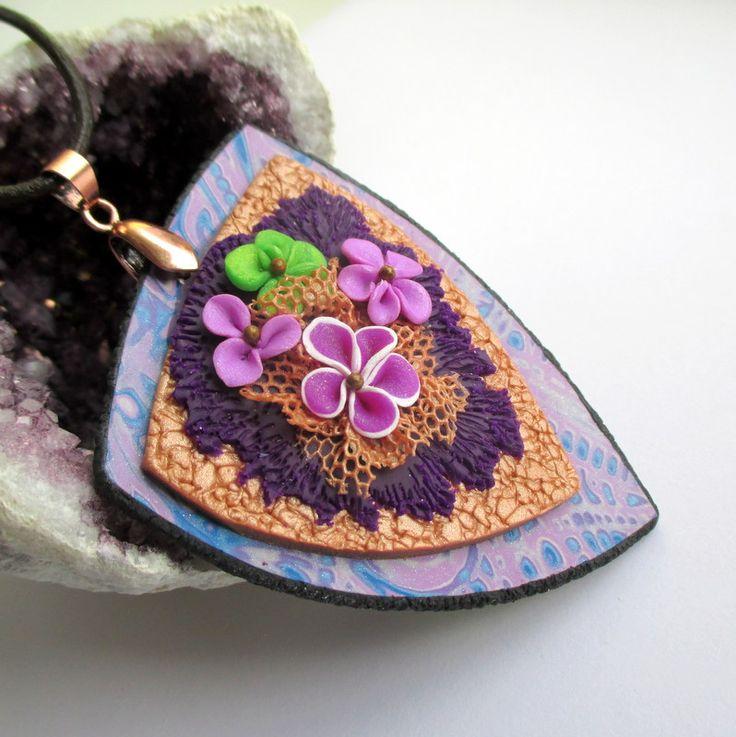 Romantický Originální přívěsek s květinovou aplikací je vyroben z polymerové hmoty Premo a je zavěšen na delší kožené šňůrce, zakončené karabinkou, jde přetáhnout i přes hlavu. Krásně se bude vyjímat na jednobarevném svetříku, halence, či tričku. Určen je spíše pro romantické dušičky :-). Určitě potěší jako dárek třeba pod stromeček :-)