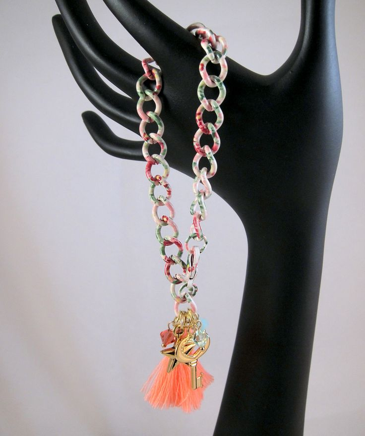 Completely unique, fun, one-of-a-kind bracelet will get you noticed! Floral print chain gives the bracelet an interesting and appealing, whimsical look. Very girly even with the chunky chain.   The floral print chain is a refreshing mix of white with pink and magenta flowers and green leaves. The pattern fits well for spring and summer. The charm dangles include a neon orange tassel, gold heart shaped key, gold star, and 3 Swarovski crystals.