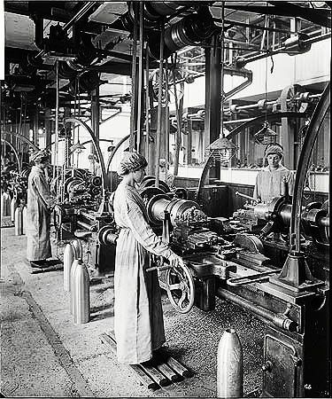In 1915 the Cunard Steamship Company's store and engineering works at Rimrose Road, Bootle, England was converted to operation as a munitions factory. The predominantly female workforce manufactured various sizes of shells. 1917 picture showing women standing on duck boards working on lathes.  I like the little cranes or lifts that they have attached to the end of each lathe bed