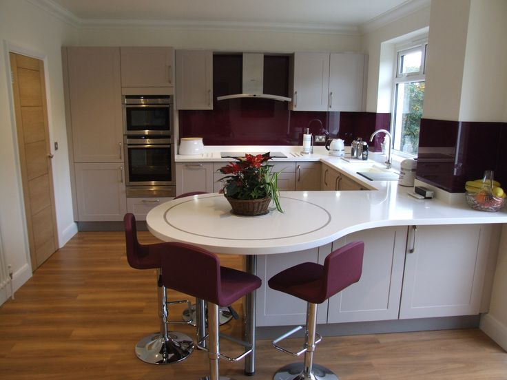 This latest installation from Colliers is extremely warm and welcoming. With Cashmere shaker style cabinetry and warm Aubergine glass splashbacks. The worktops are Glacier White Corian with a decorative circular inlay on the Pensinsula. The stools co-ordinate beautifully with the colour scheme in this room. #German #Kitchen #Cashmere #Shaker #Corian #GlacierWhite #Clay #Aubergine #Cancio #Stools #WoodFlorring #Neff #Appliances