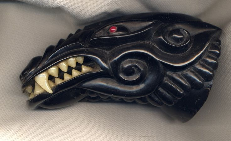 A wolf head drinking horn with inlaid carved bone teeth.