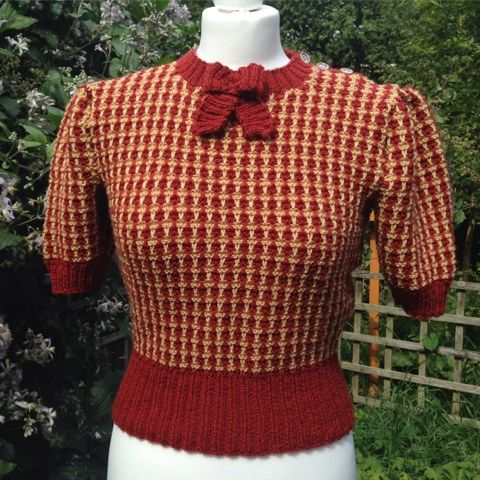 Almost Houndstooth pattern, 3 buttons on left shoulder.