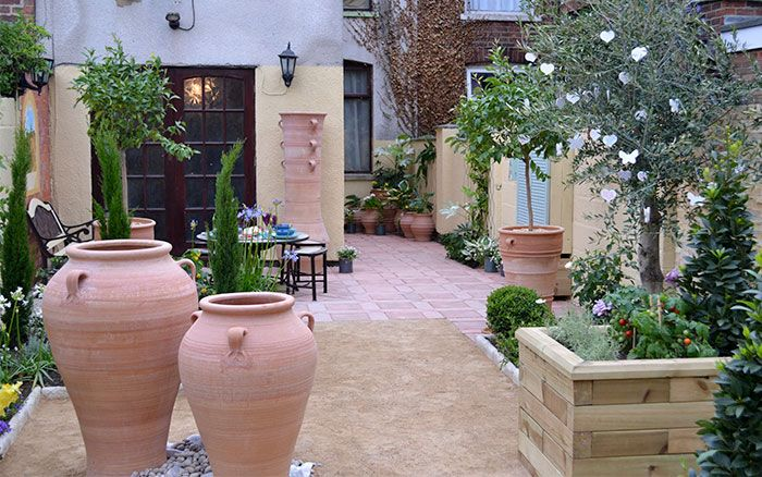 Beautiful Mediterranean garden with terracotta pots and patio and olive trees.