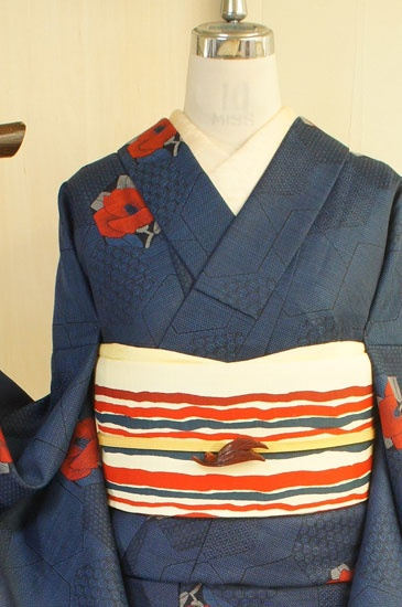 黒と紺青の糸が織りなす濃紺の地に、模様もとりどりな亀甲形の裂を切りばめたような幾何学デザインと、深い赤が美しく映える椿模様が織り出されたウールの単着物です。