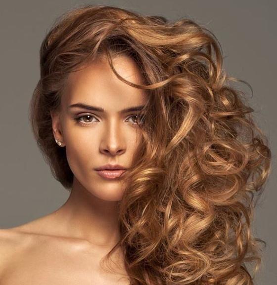 Les cheveux de cette femme sont magnifiques et ils ont été coiffés de manière à les mettre en valeur. Ainsi, ils ont été ramenés d'un côté, permettant aux longues mèches bouclées de descendre sur une épaule. La coloration brune a été éclaircie de plusieurs mèches brun pâle.