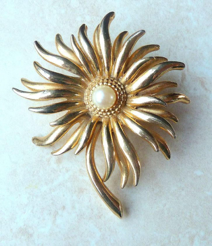 A beautiful, vintage, layered floral brooch by Sphinx. The brooch is designed with alternating lengths, of layered petals, radiating from a central faux pearl bead. The layering of the brooch creates a stunning 3D effect. The brooch is set in gold tone metal with a faux pearl bead to the center. The brooch is an early, very collectable Sphinx design.