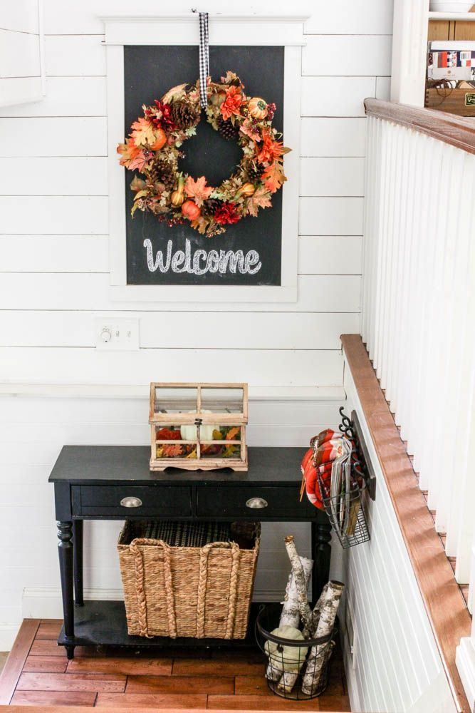 Planked walls in split level entryway with chalkboard and fall decor…
