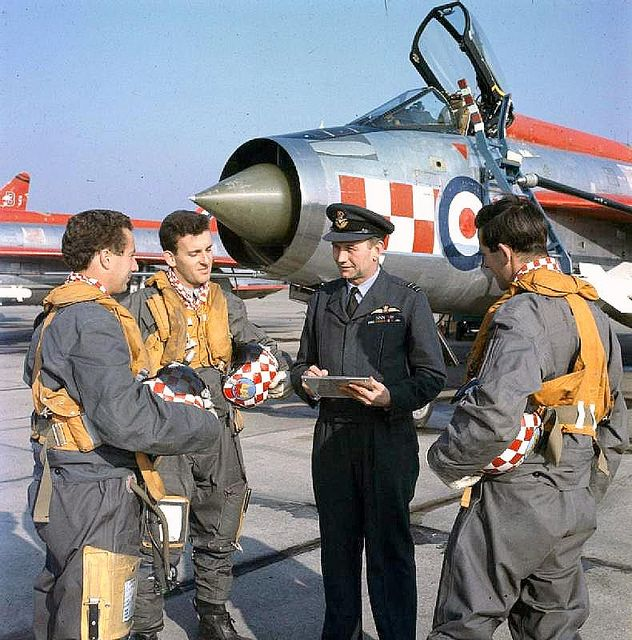 Wing Commander B H Howard, Wing Commander Flying at RAF Wattisham, discussing a sortie with Flight Lieutenant J M Curry on his lefft and Flight Lieutenant B J Cheater on his right in front of No 56 Squadron's English Electric Lightning F1As.