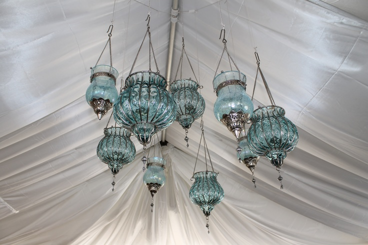Tiffany blue lanterns hanging from the tent ceiling, through the satin draping.